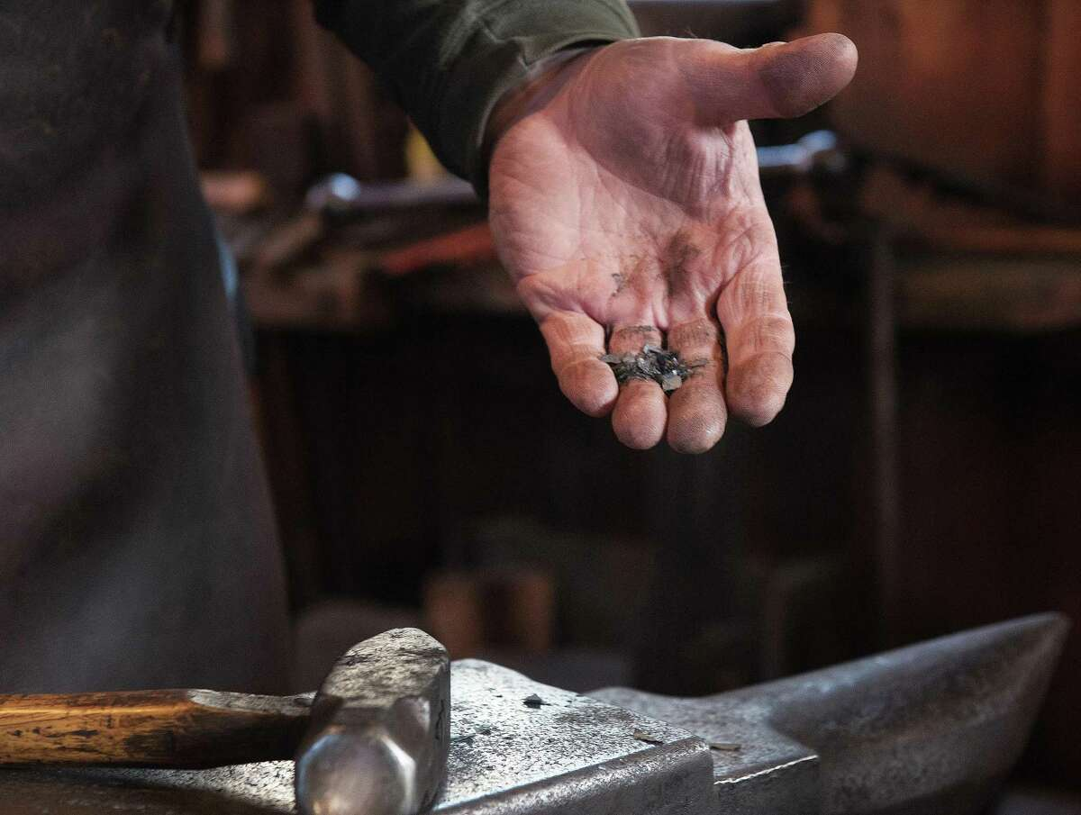 Blacksmith Skip Kern holds the residue from his hammering out a hook at Wilton Historical Society.