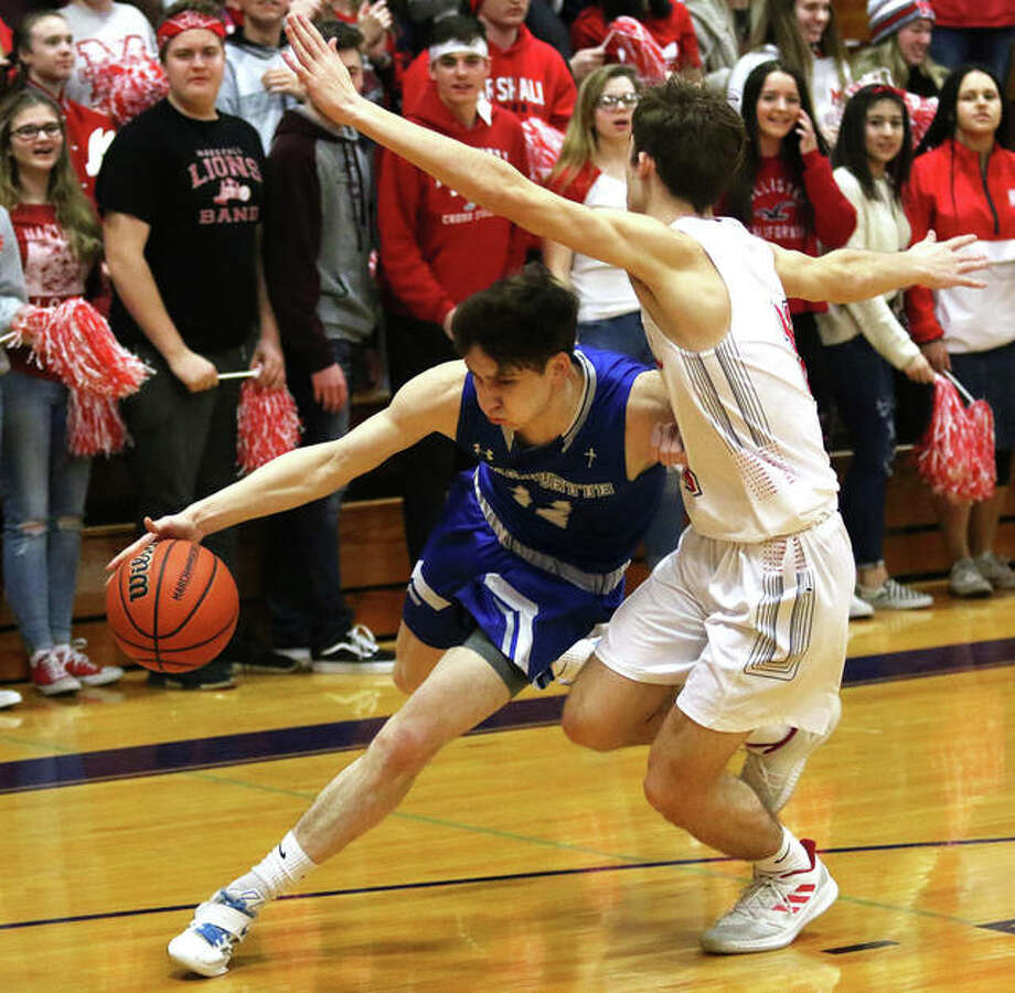 Marquette Catholic's Spencer Cox (left) drives on Marshall's Daniel Tingley in the first half of a Shelbyville Class 2A Sectional semifinal boys basketball game Tuesday night. Photo: Greg Shashack / The Telegraph