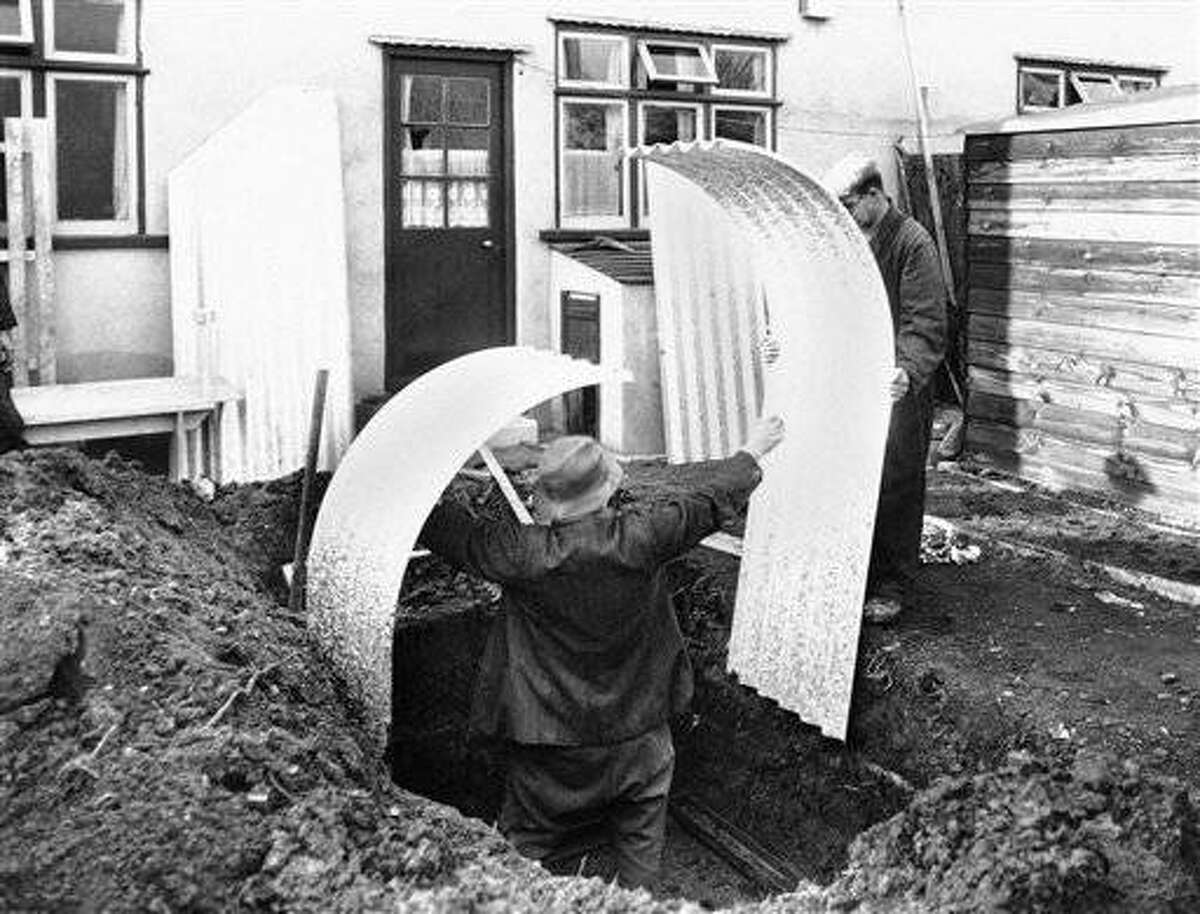 Here is how a Londoner, one alarmed eye cocked on Germany and Italy and the other Spain, may build his own family air raid shelter in the privacy of his own back yard, March 4, 1939. The whole bombproof outfit steel parts, nuts and bolts and even a wrench comes to him in one package with directions. First he digs a hole which is three feet deep and looks ironically like a grave then these sheet sections are placed on steel foundation channels sunk in the ground. (AP Photo)