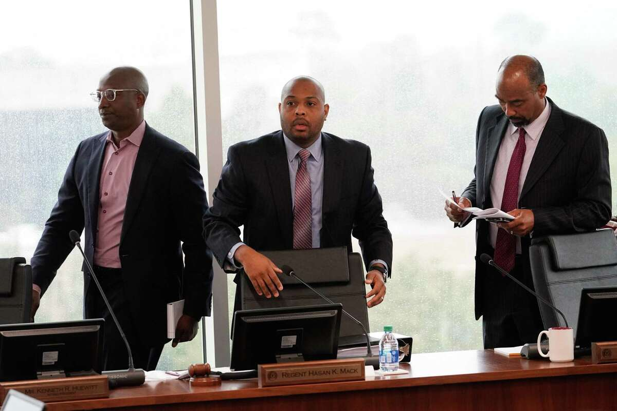 Texas Southern University's board of regents Derrick Mitchell, left, Hasan Mack, chair, and Albert Myers, vice chair, right, leave board meeting for an executive session Thursday, Feb. 19, 2020 in Houston. The board is meeting for the first time since giving their notice of termination for sidelined TSU president Austin Lane earlier this month.