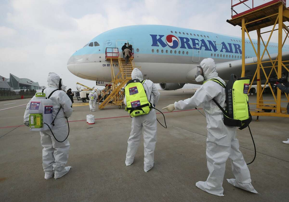 Workers wearing protective gear arrive to disinfect the airplane for New York as a precaution against the new coronavirus at Incheon International Airport in Incheon, South Korea, Wednesday, March 4, 2020. the coronavirus epidemic shifted increasingly westward toward the Middle East, Europe and the United States on Tuesday, with governments taking emergency steps to ease shortages of masks and other supplies for front-line doctors and nurses. (Suh Myoung-geon/Yonhap via AP)