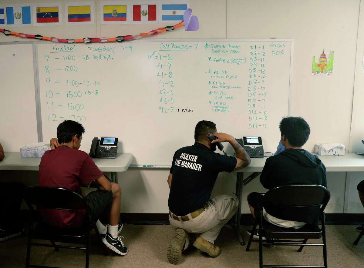 Staff help immigrants make calls to family at the U.S. government's newest holding center for migrant children in Carrizo Springs in July 2019. The Trump administration is now fast-tracking the legal proceedings of thousands of immigrant children in its care, including unveiling a pilot program in Houston to stream their hearings through video technology - a move advocates say will jeopardize their asylum cases and speed up deportations.