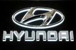 FILE - In this Feb. 14, 2019 file photo, this is the Hyundai logo on a sign at the 2019 Pittsburgh International Auto Show in Pittsburgh. Hyundai is joining affiliated automaker Kia in yet another U.S. recall for problems that could cause engine fires.Hyundai says Wednesday, March 4, 2020, that it's recalling nearly 207,000 Sonata midsize cars from 2013 and 2014 because a hose that connects one fuel pump to another can develop cracks, leak fuel and potentially cause a fire. (AP Photo/Gene J. Puskar, File)