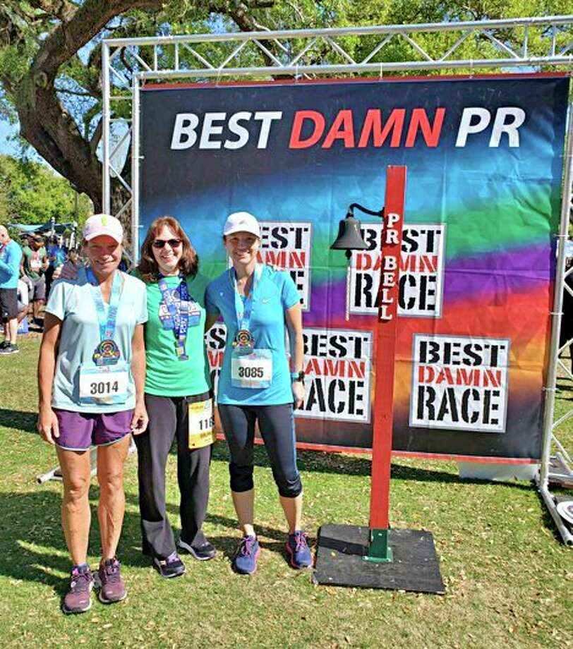 Pictured (from left to right) are Donna Ervin, Jan Hopwood and Stephanie Quinn, posing with their medals after the Best Damn Race Orlando half marathon. (Courtesy photo)