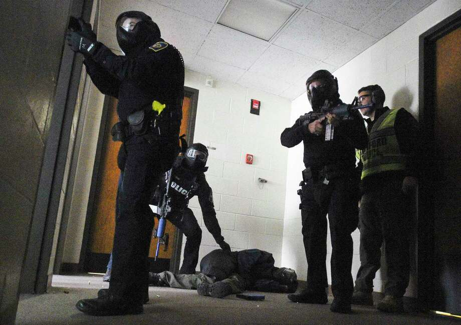 Officers from the Stamford Police Department run through an Active Shooter scenario during a training drill on Wednesday in Stamford. Officers from the departments Special Response Team (SWAT) went through various controlled situations involving a shooter, to officer rescues situations. Photo: Matthew Brown / Hearst Connecticut Media / Stamford Advocate