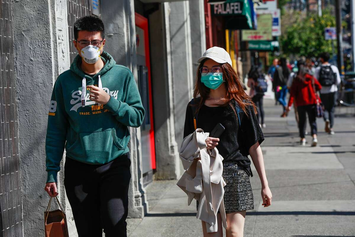 A man and woman wear masks while walking on Durant Avenue near the UC Berkeley campus on Wednesday, March 4, 2020 in Berkeley, California. A Berkeley resident recently tested positive to the coronavirus.