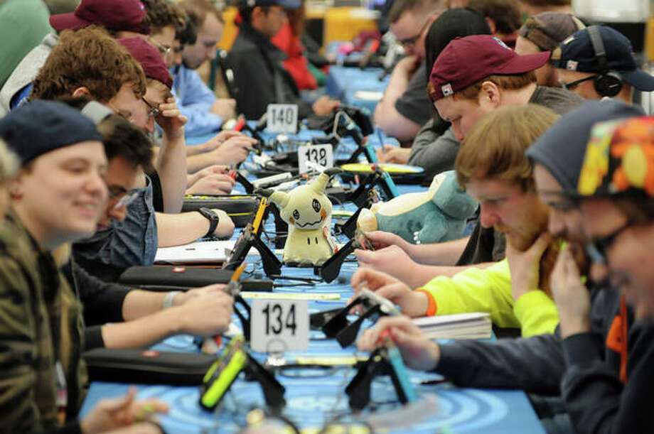 A plush Pokémon figure stands vigil as a table of contestants face off during the Pokemon Regional Championships. Players brought their portable game systems and many carried or wore plush Pokémon characters. Photo: David Blanchette|For The Intelligencer