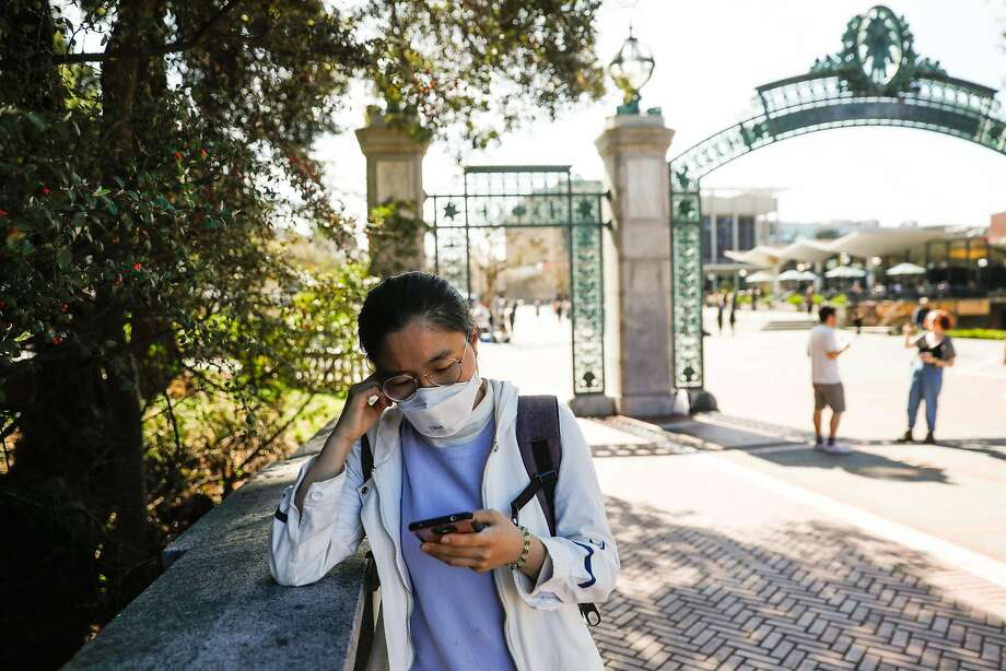 Student Joy Li wears a mask as she reads about the coronavirus on her phone on the UC Berkeley campus on March 4, 2020. Photo: Gabrielle Lurie / The Chronicle