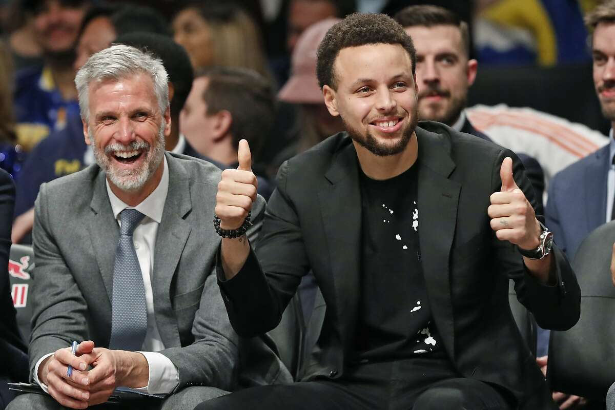"""ADDS NAME OF ASSISTANT COACH - Golden State Warriors Stephen Curry, right, gives a thumbs-up to a Brooklyn Nets fan known as """"Mr. Whammy"""" during the second half of an NBA basketball game Wednesday, Feb. 5, 2020, in New York. At left is Warriors assistant coach Bruce Fraser. Curry is recovering from a hand injury. (AP Photo/Kathy Willens)"""