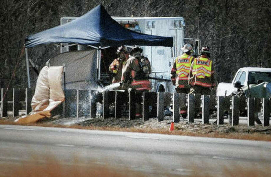 Lincoln firefighters wash down fuel Tuesday after the crash of a small airplane in the southbound lane of I-55 over Illinois 121 in Lincoln. Photo: David Proeber | The Pantagraph Via AP