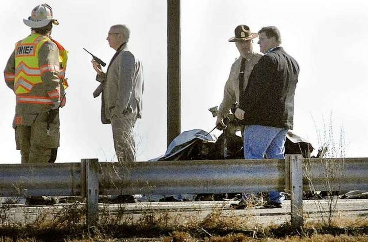 Lincoln firefighters wash down fuel Tuesday after the crash of a small airplane in the southbound lane of I-55 over Illinois 121 in Lincoln. Photo: David Proeber   The Pantagraph Via AP