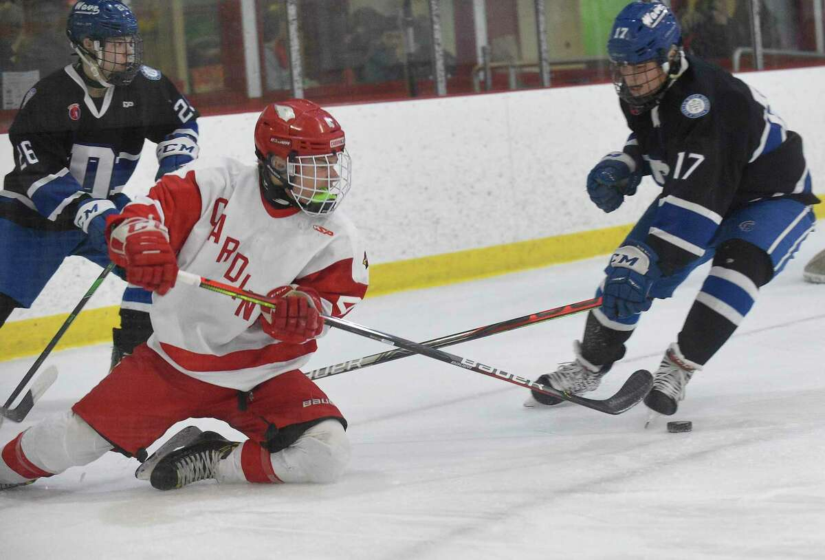 Greenwich's Jack Shreders (4) battles for the puck with Darien's Luke johnston (26) and Jamison Moore (17) in the first period of an FCIAC Boys Hockey semifinal game at Hamill Rink on March 4, 2020 in Greenwich, Connecticut.