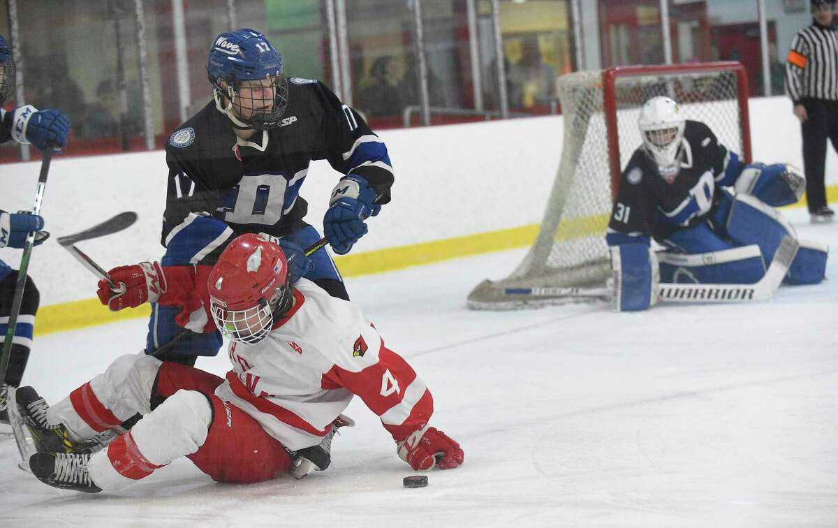Greenwich's Jack Shreders (4) battles for the puck with Darien's Jamison Moore (17) in the first period of an FCIAC Boys Hockey semifinal game at Hamill Rink on March 4, 2020 in Greenwich, Connecticut.