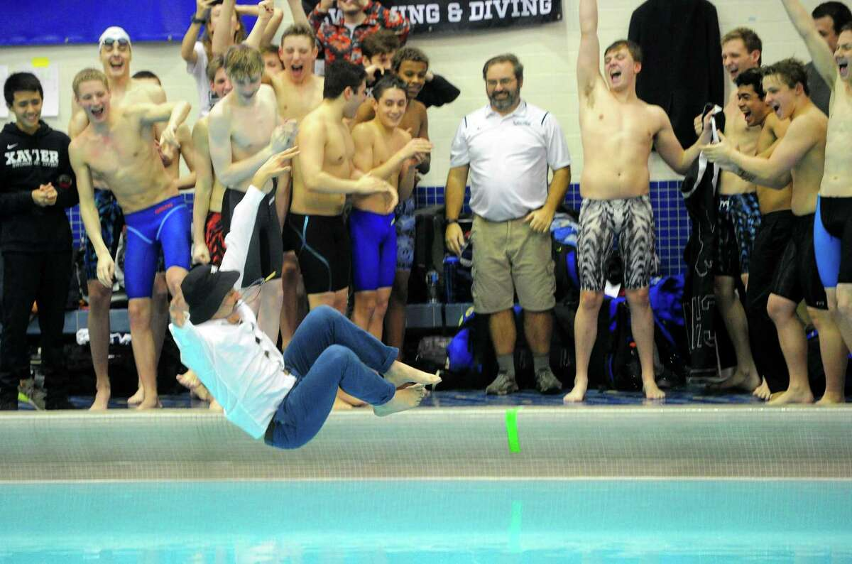 Xavier coach Ronald Vaughan leaps into the pool after the school won the SCC boys swimming championship at Southern Connecticut State University in New Haven on Wednesday.