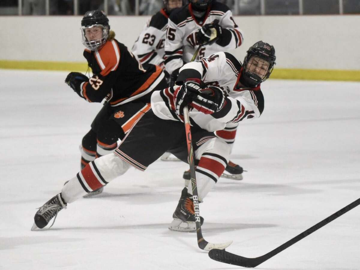 New Canaan's Shane Mettler (14) cuts into the zone against Ridgefield during the FCIAC boys ice hockey semifinals at the Darien Ice House on Wednesday.