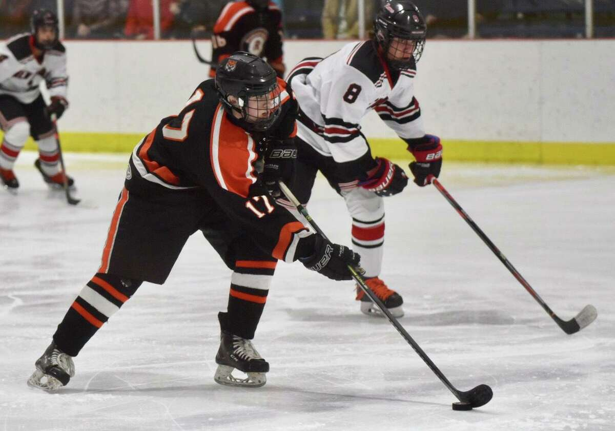 Ridgefield's Will Stewart (17) skates toward the net with New Canaan's Griffin Deane (8) in pursuit during the FCIAC boys ice hockey semifinals at the Darien Ice House on Wednesday.