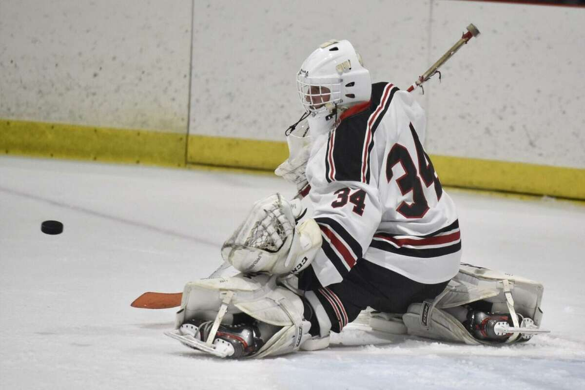 New Canaan goalie Beau Johnson makes a save against Ridgefield during the FCIAC boys ice hockey semifinals at the Darien Ice House on Wednesday, March 4, 2020.
