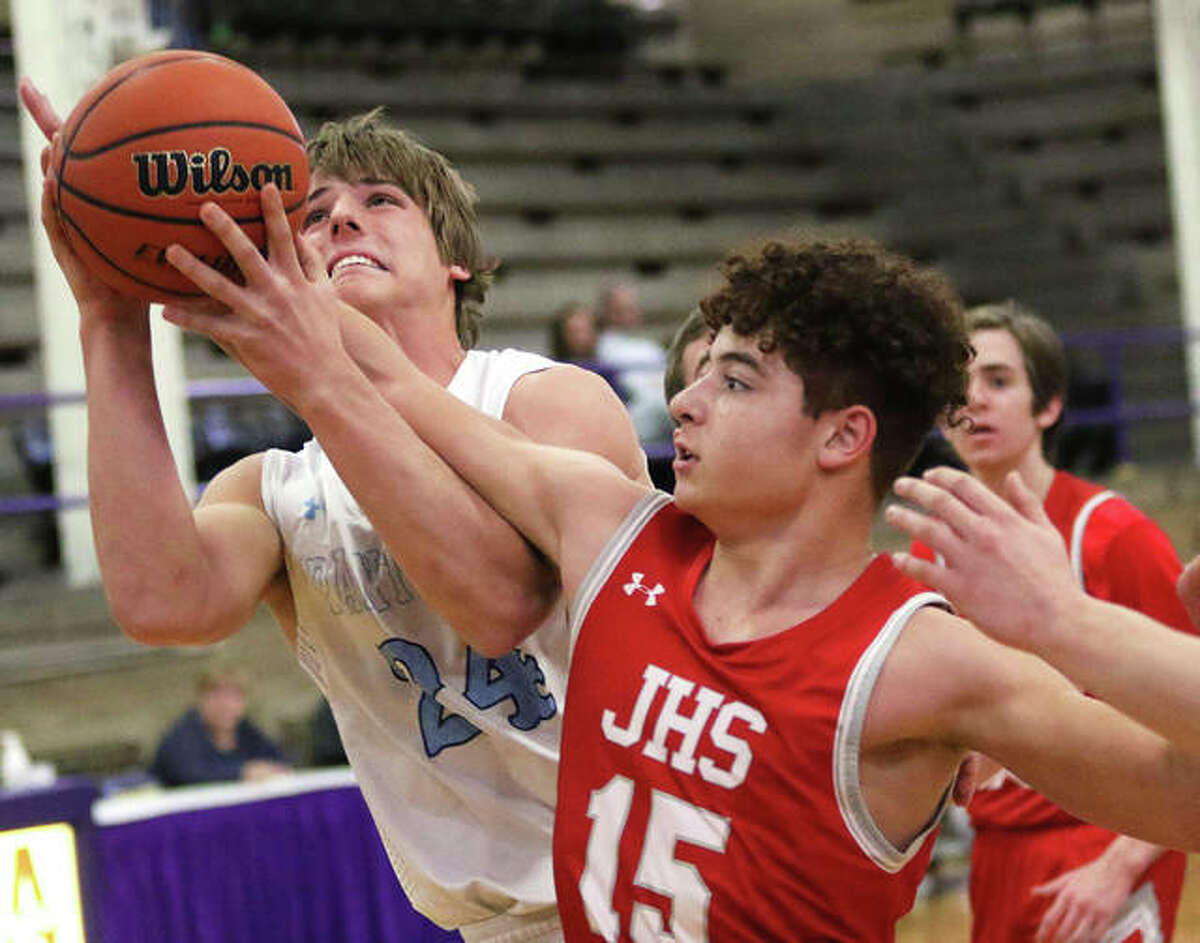 Jersey's Matthew Jackson (left) goes up for a shot and is fouled by Jacksonville's Elijah Owens in the first quarter Wednesday night in a semifinal at Taylorville Class 3A Regional.