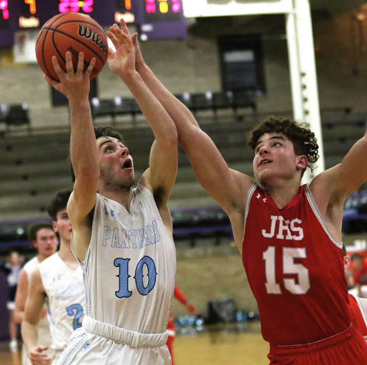 Jersey's Garrett Carey (10) scores while Jacksonville's Elijah Owens contests the shot Wednesday night in a semifinal at Taylorville Class 3A Regional.