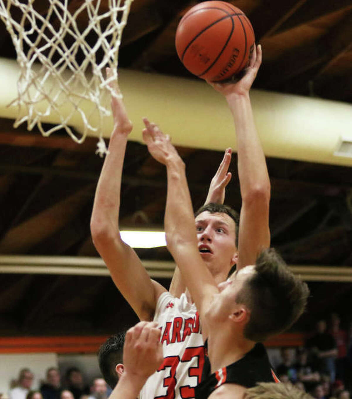 Calhoun's Corey Nelson (33) shoots over a Raymond Lincolnwood defender during Friday's championship game at the Lincolnwood Class 1A Regional in Raymond. On Wednesday night at Dupo, the Warriors' season ended with a loss to Winchester West Central.