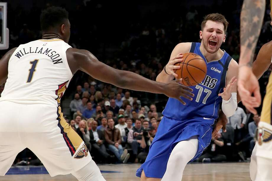 The Mavericks' Luka Doncic (77) drives against the Pelicans' Zion Williamson. Donsic had a triple-double in the victory. Photo: Tom Pennington / Getty Images