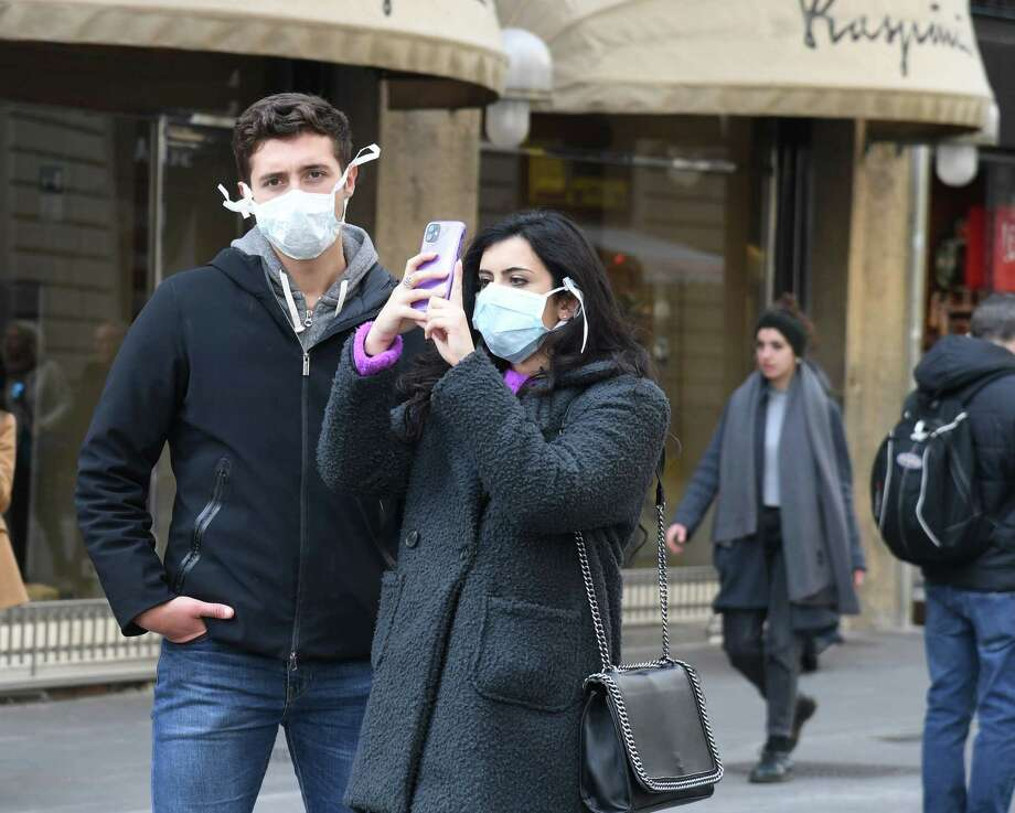 Tourists with protective masks visit Florence, Italy on February 25, 2020. The Stamford-based American Institute for Foreign Study, which canceled its programs in the past semester in Florence and Rome, received a PPP loan between $2 million and $5 million. Photo: CARLO BRESSAN / AFP Via Getty Images / AFP or licensors