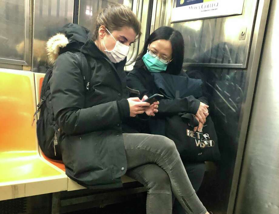 In this March 4, 2020 photo, two women wear masks as they ride a subway train, in New York. Two more cases of the new coronavirus have been confirmed in New York City, raising New York state's total to 13, Mayor Bill de Blasio said Thursday. (AP Photo/Richard Drew) Photo: Richard Drew / Associated Press / Copyright 2020 The Associated Press. All rights reserved