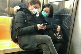 In this March 4, 2020 photo, two women wear masks as they ride a subway train, in New York. Two more cases of the new coronavirus have been confirmed in New York City, raising New York state's total to 13, Mayor Bill de Blasio said Thursday. (AP Photo/Richard Drew)