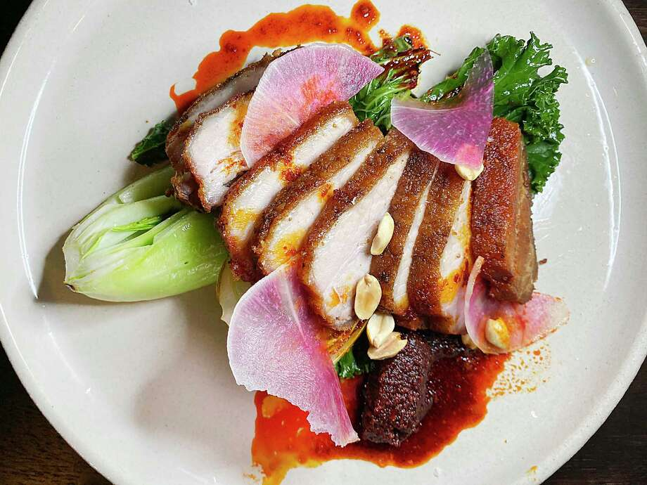 Crispy pork belly incorporates braised gai lan, kale, hot chile oil, peanuts and watermelon radish at The Magpie, a small Korean-inspired restaurant on East Houston Street. Photo: Mike Sutter /Staff