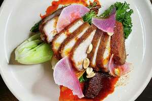 Crispy pork belly incorporates braised gai lan, kale, hot chile oil, peanuts and watermelon radish at The Magpie, a small Korean-inspired restaurant on East Houston Street.