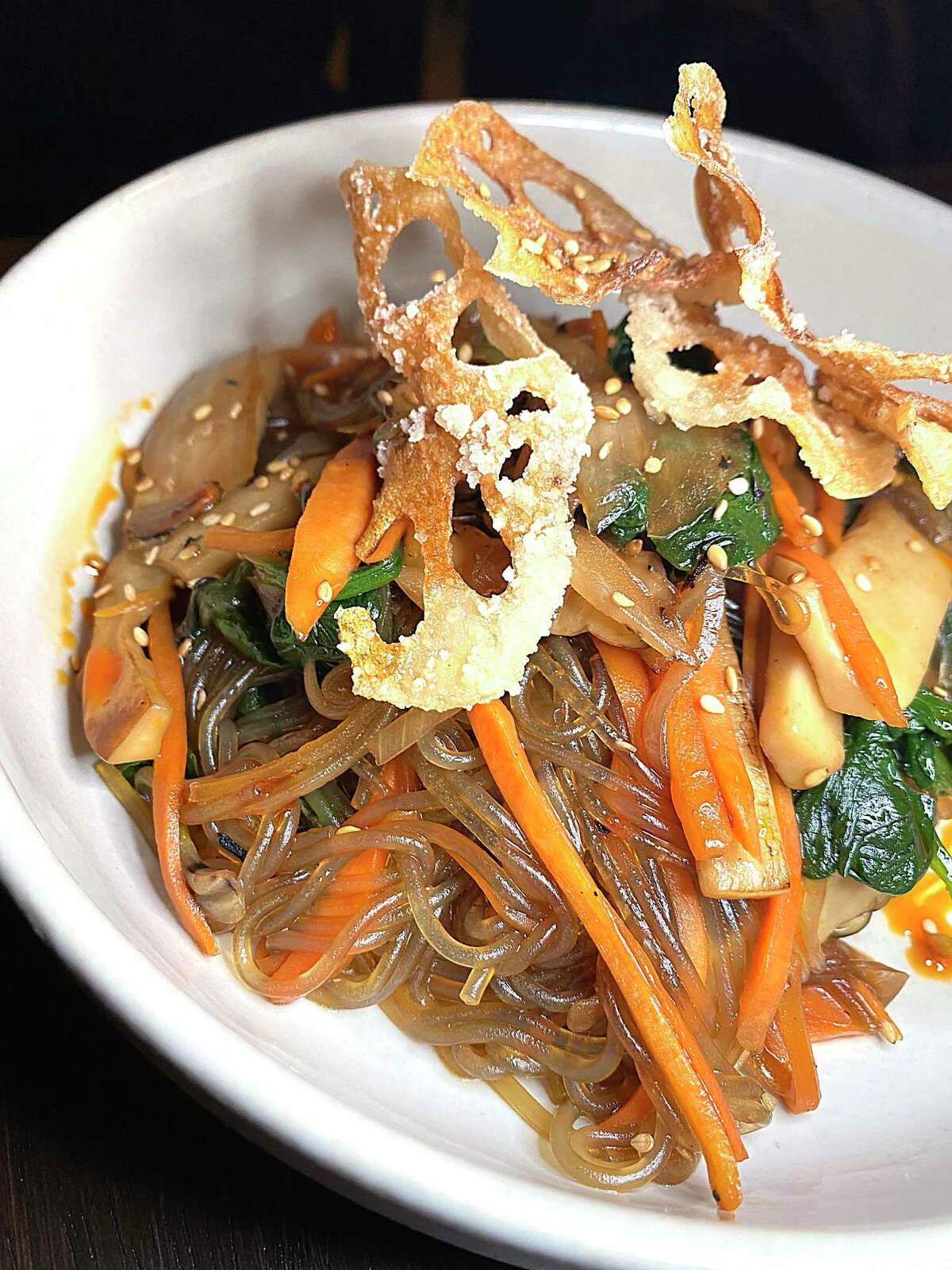 Japchae incorporates sweet potato glass noodles, spinach, carrots, onions and fried lotus chips at The Magpie.