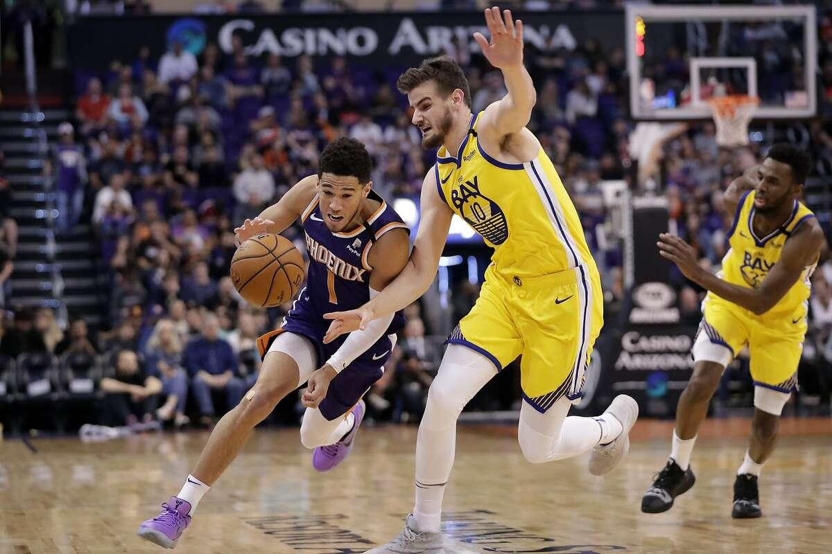 Phoenix Suns guard Devin Booker (1) drives past Golden State Warriors forward Dragan Bender (10) during the second half of an NBA basketball game Saturday, Feb. 29, 2020, in Phoenix. (AP Photo/Matt York)
