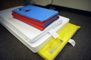 A selection of baby changing and sleeping mats are stacked on an office floor.