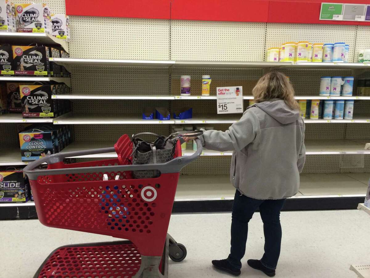A shopper scans the shelves for sanitizing wipes last week at the Target store in Hawley Lane Mall in Trumbull.