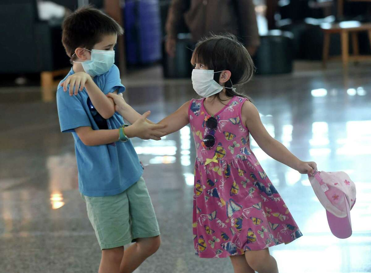 Two children wearing facemasks play in front of the departure area of Ngurah Rai airport in Denpasar on February 8, 2020.