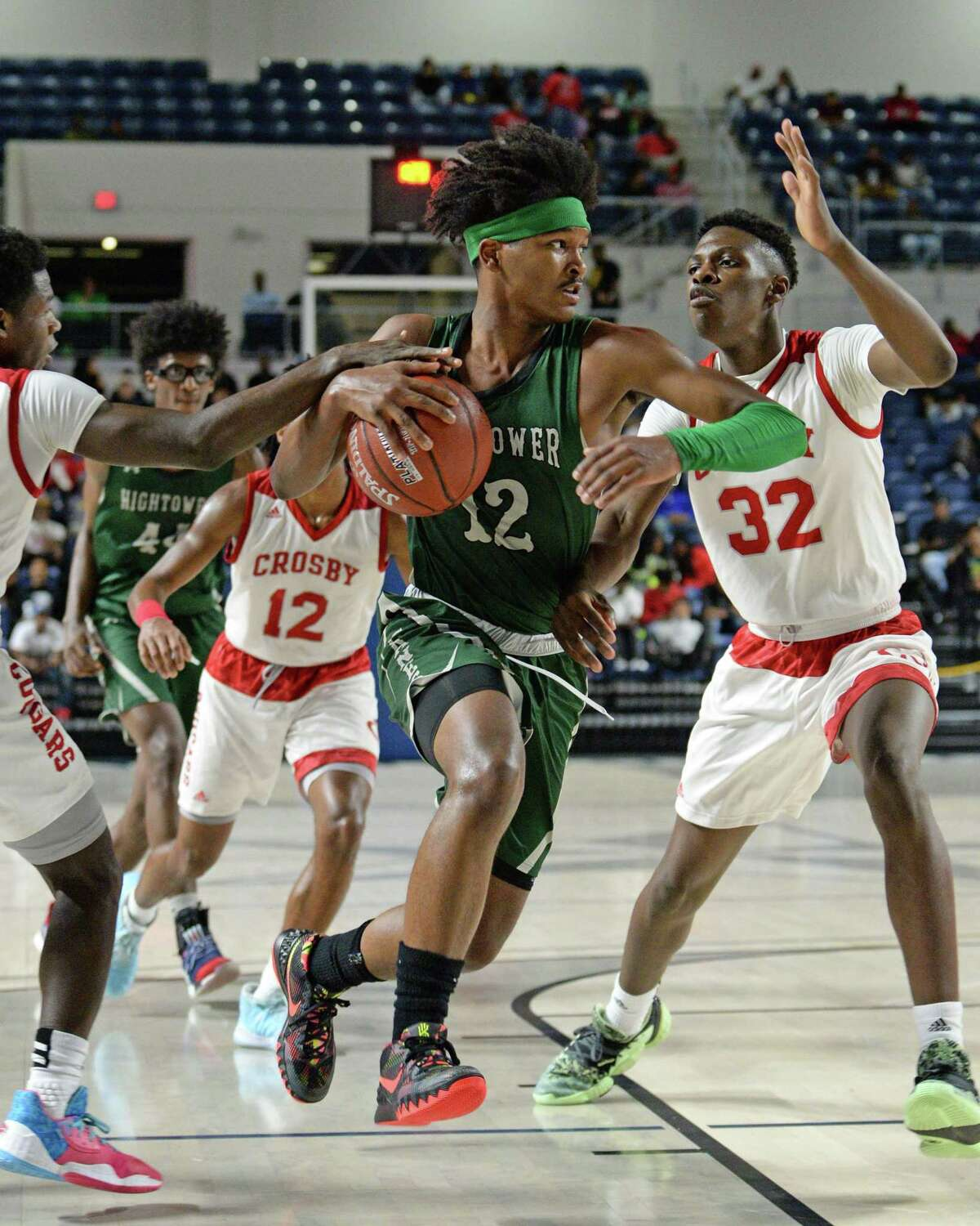 Bryce Griggs (12) of Hightower drives between multiple cougar defenders during the third quarter of the Boys 5A Region III Quarterfinal basketball game between the Hightower Hurricanes and the Crosby Cougars on Tuesday, March 3, 2020 at Delmar Fieldhouse, Houston, TX.