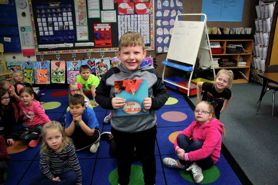Bad Axe Elementary first-grade student Cooper Bushey poses with a new book, donated by the Huron County Farm Bureau. (Sara Eisinger/Huron Daily Tribune)