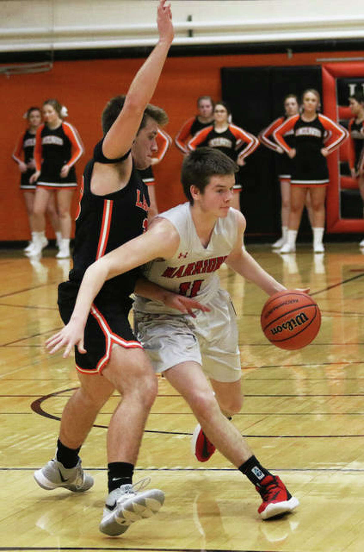 Calhoun's Stone Zirkelbach (right) dribbles past a Raymond Lincolnwood defender in Friday's championship game at the Lincolnwood Class 1A Regional in Raymond.