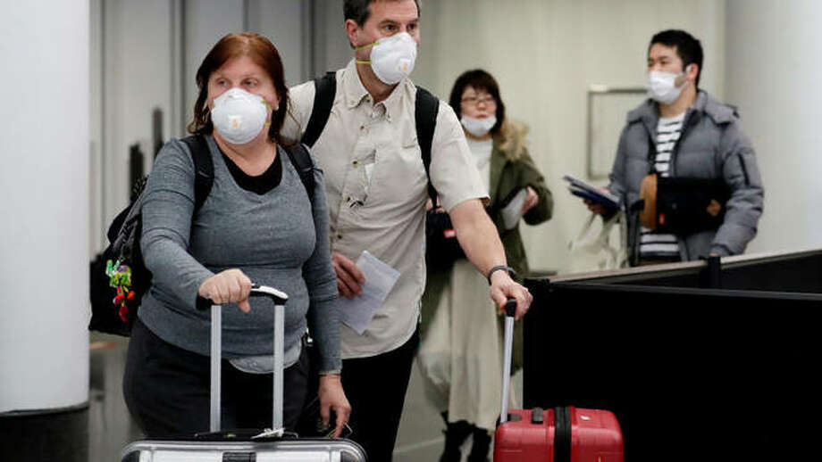 Travelers wear protective mask as they walk through in terminal 5 at O'Hare International Airport in Chicago, Sunday, March 1, 2020. (AP Photo/Nam Y. Huh)