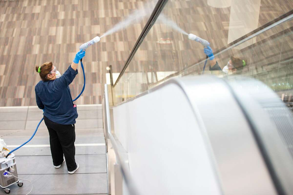 Evelin Rivera uses an electrostatic cleaner at Moscone Center South, Friday, Feb. 14, 2020, in San Francisco, Calif.