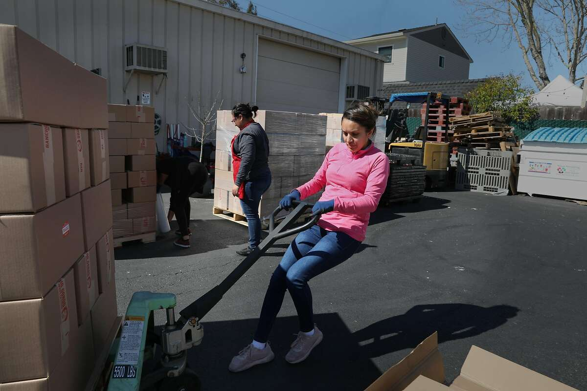 Shipping manager Adriana Barajas (pink shirt) brings six pallets of beans prepared for Fed Ex pickup today in the parking lot next to the factory of bean supplier Rancho Gordo seen on Wednesday, March 4, 2020, in Napa, Calif.