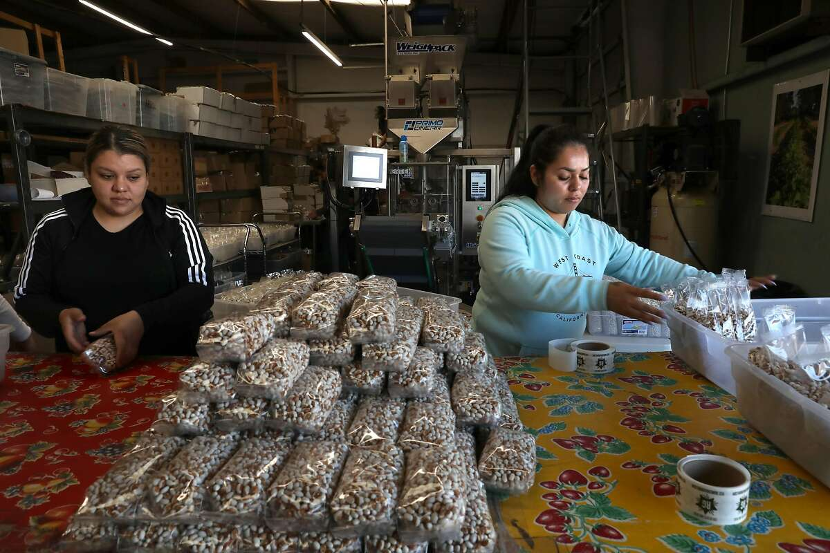 Staff including Griselda Molinero (right) pack beans in the factory of bean supplier Rancho Gordo seen on Wednesday, March 4, 2020, in Napa, Calif.