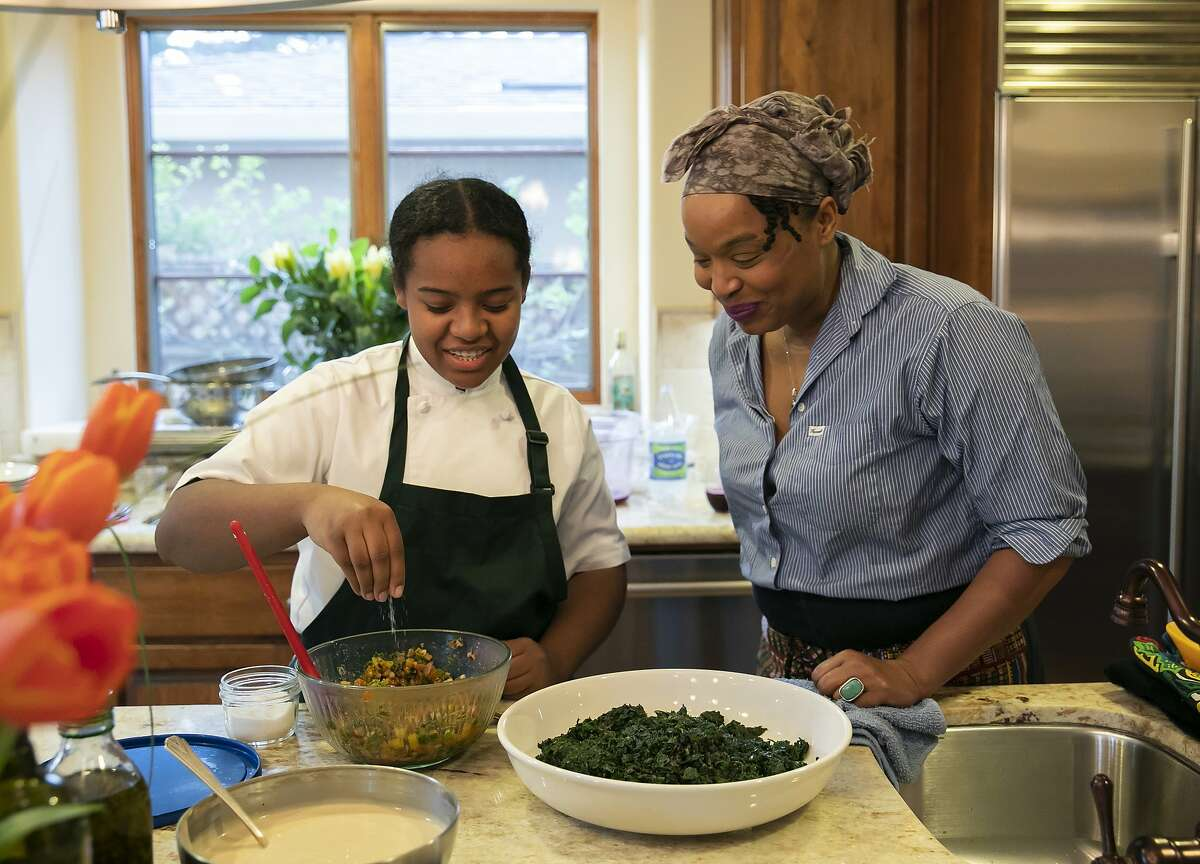 Chef Monifa Dayo, right, watches as Chef Rahanna Bisseret Martinez, 16, left, puts the finishing touches on her Texas Caviar topped with Garlic Oil dish for a dinner party at the home of Michele and Harry Elam on Saturday, Feb. 29, 2020 in Redwood City, Calif.