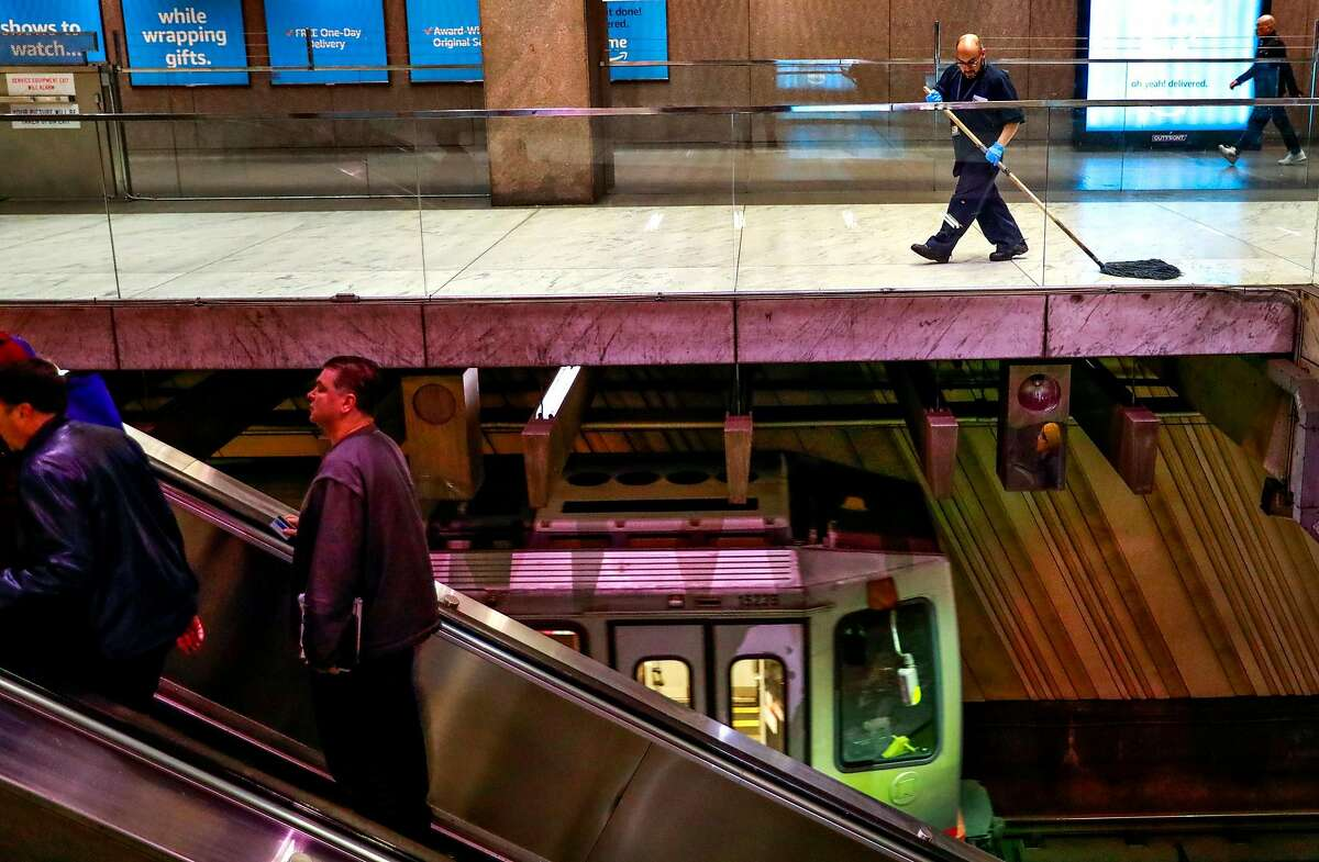 Damian V. Nabong (right) mops the floors at the Embarcadero BART station on Thursday, March 5, 2020 in San Francisco, California. BART is taking precautionary measures to prepare for the potential spread of Coronavirus.
