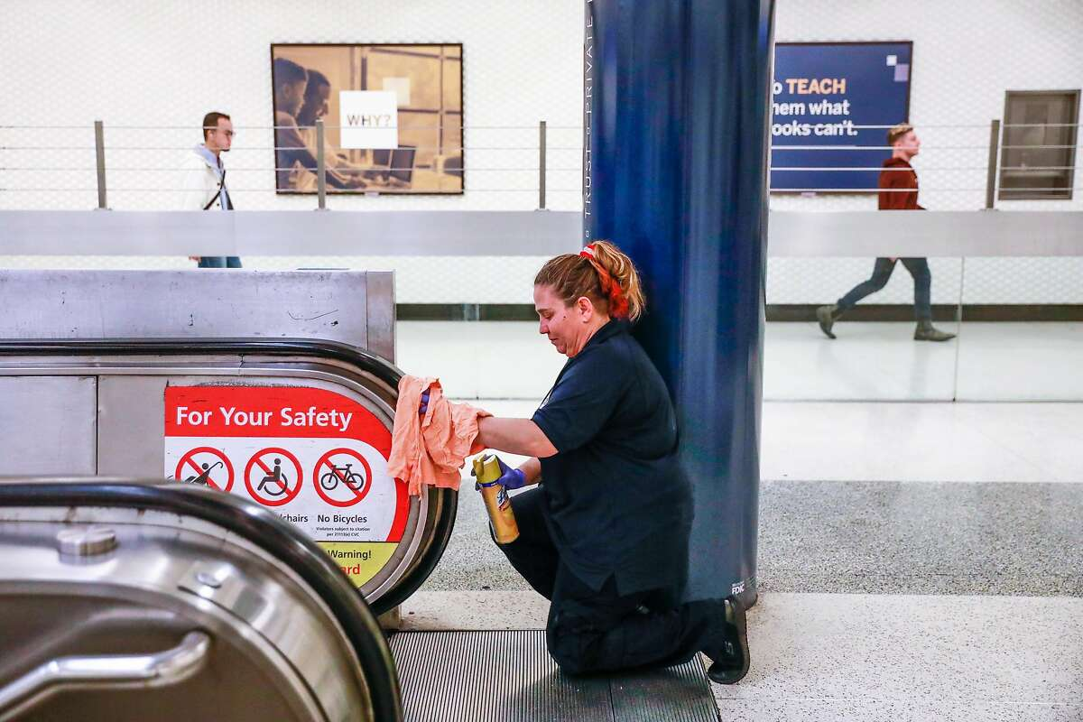 Bobbi Vittori wipes clean the escalator railing at the Montgomery BART station on Thursday, March 5, 2020 in San Francisco, California. BART is taking precautionary measures to prepare for the potential spread of Coronavirus.