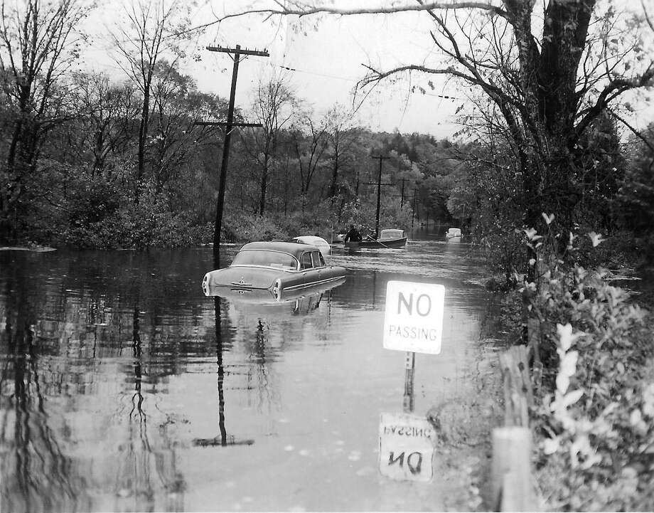 Cars were left swamped and a boat made its way down Route 7 after the big flood of 1955 Photo: Contributed Photo / Ridgefield Historical Society