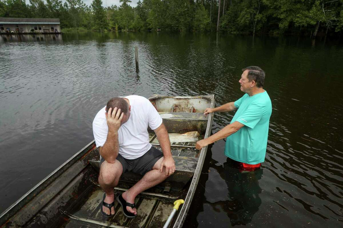 """Stephen Gilbert, left, and his father-in-law sit in front of their flooded property on Friday, Sept. 20, 2019, in the Mauriceville, Texas, area. Floodwaters are starting to recede in most of the Houston area after the remnants of Tropical Storm Imelda flooded parts of Texas. """"I'm on my third house,"""" said Gilbert, who lives behind his father-in-law. """"I wouldn't go anywhere else in the world,"""" he said. """"All we have is family anyway."""" ( Jon Shapley/Houston Chronicle via AP)"""