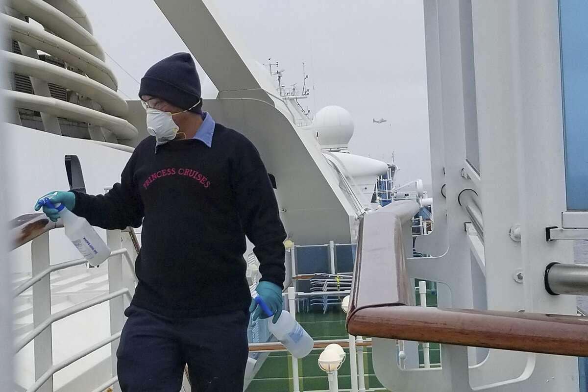 In this photo provided by Michele Smith, a cruise ship worker cleans a railing on the Grand Princess Thursday, March 5, 2020, off the California coast. Scrambling to keep the coronavirus at bay, officials ordered a cruise ship with about 3,500 people aboard to stay back from the California coast Thursday until passengers and crew can be tested, after a traveler from its previous voyage died of the disease and at least two others became infected. A California Air National Guard helicopter lowered test kits onto the 951-foot (290-meter) Grand Princess by rope as the vessel lay at anchor off Northern California, and authorities said the results would be available on Friday. Princess Cruise Lines said fewer than 100 people aboard had been identified for testing. (Michele Smith via AP)