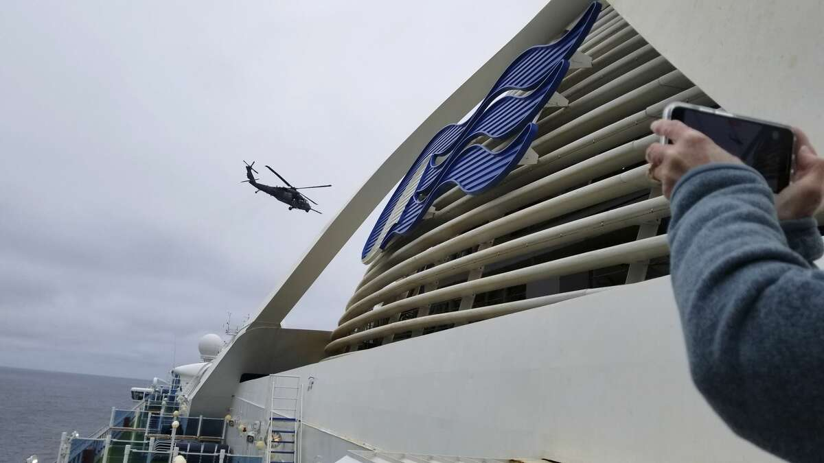 In this photo provided by Michele Smith, a California Air National Guard  helicopter delivering virus testing kits hovers above the Grand Princess cruise ship Thursday, March 5, 2020, off the California coast. Scrambling to keep the coronavirus at bay, officials ordered a cruise ship with about 3,500 people aboard to hold off the California coast Thursday until passengers and crew could be tested, after a traveler from its previous voyage died and at least one other became infected. Princess Cruises says fewer than 100 of those aboard have been identified for testing. (Michele Smith via AP)