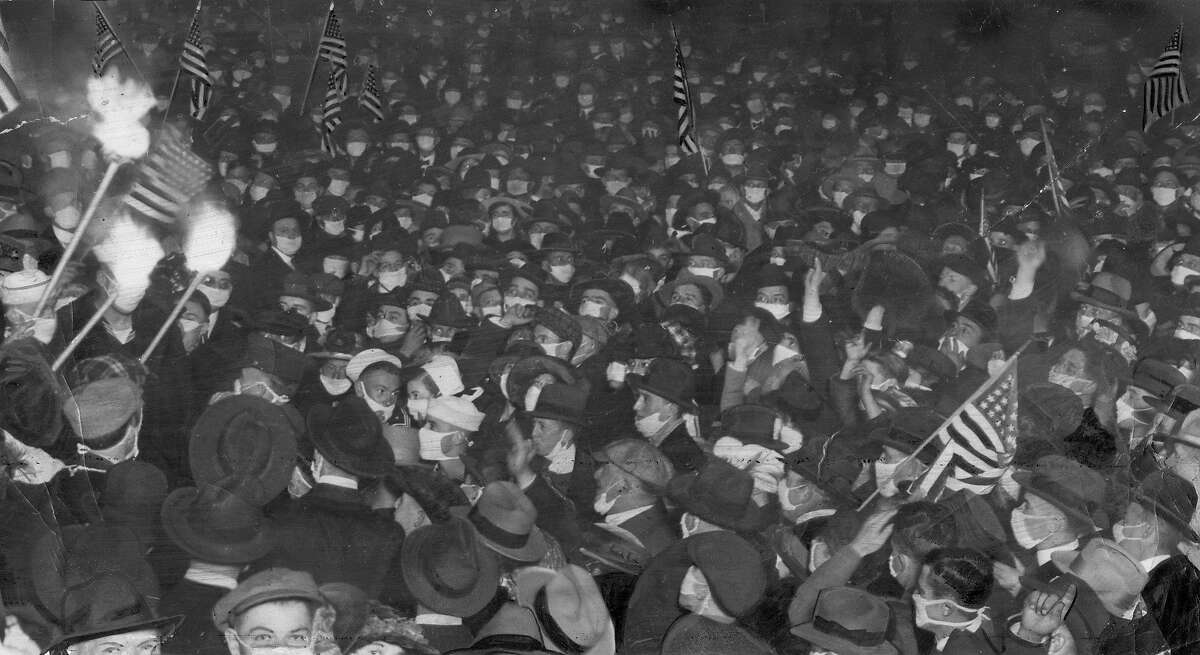 San Francisco residents celebrate the end of World War I on Nov. 11, 1918 with banners and torches and surgical masks. Weeks earlier masks became mandatory in the streets of the city, to halt the threat of the Spanish influenza.